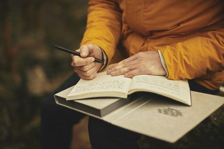 man writing in journal