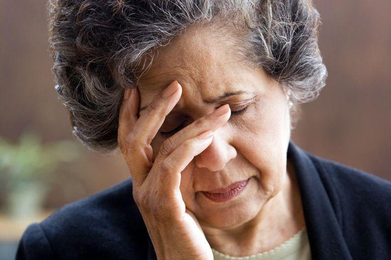 Senior Hispanic woman with head in hand