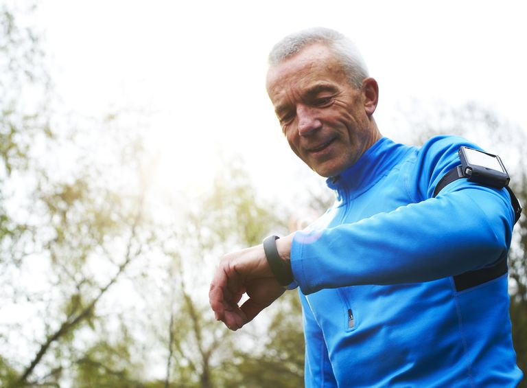 Mature male runner standing in woods looking at health monitor bracelet linked to his smart phone to track calories, steps and progress.
