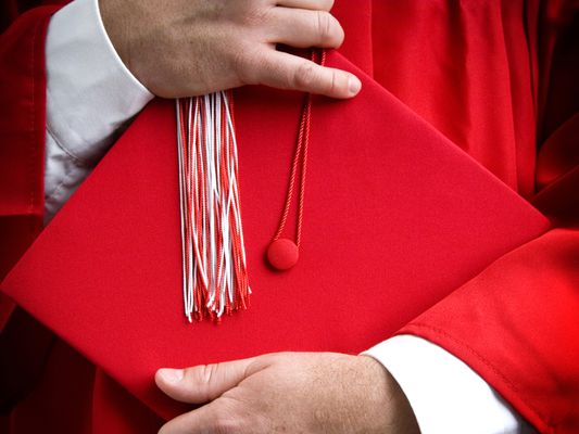 man holding red graduation cap