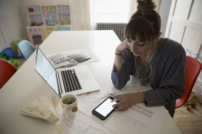 Interior designer working at laptop at dining room table listening to mp3 player
