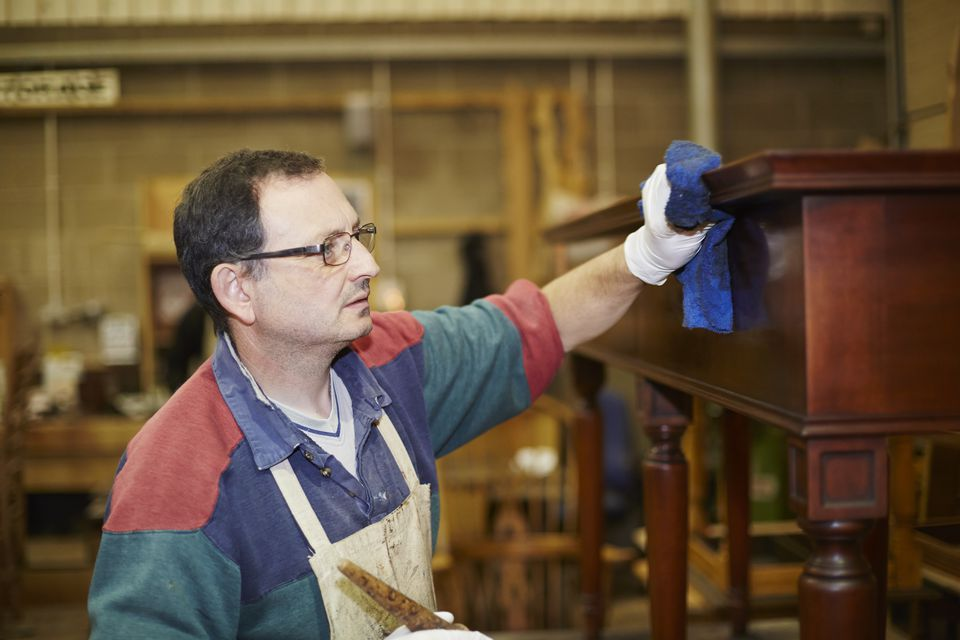 Craftsman applying wax finish to furniture