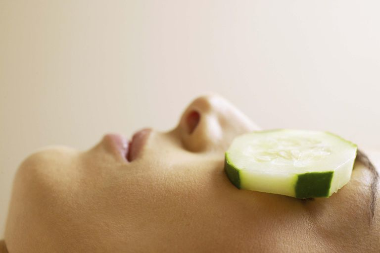 Woman with cucumber slices covering eyes