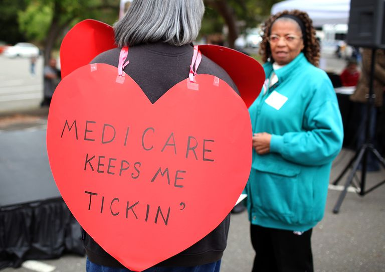 Woman wearing a heart-shaped sign reading 'Medicare Keeps Me Ticking'