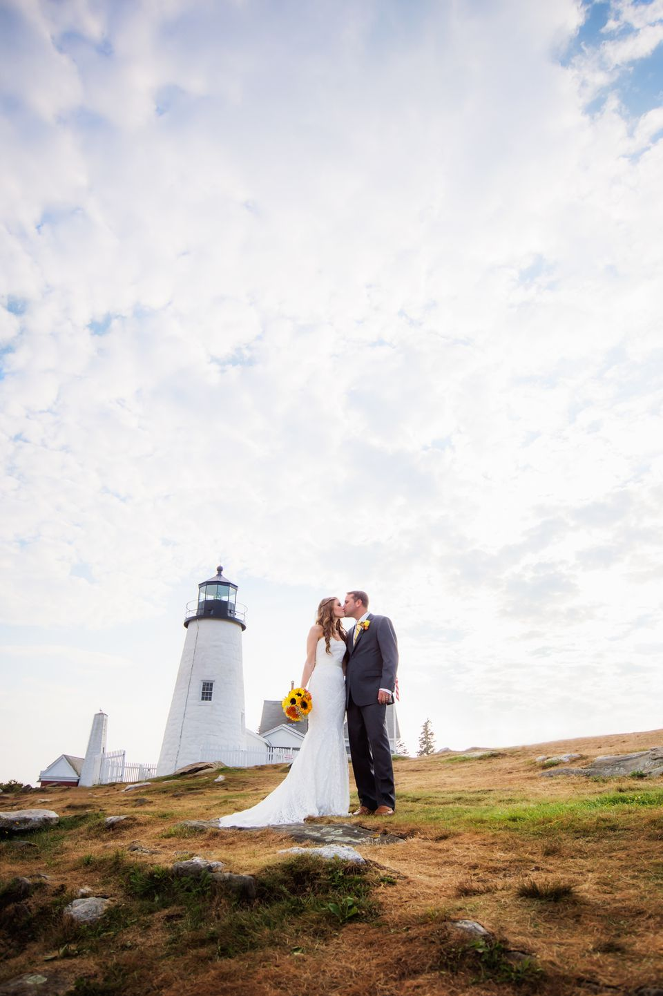 USA, Maine, Bristol, Portrait of married couple kissing, lighthouse in background