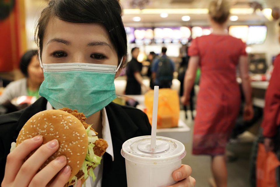 Woman wearing hygiene mask in fast food restaurant