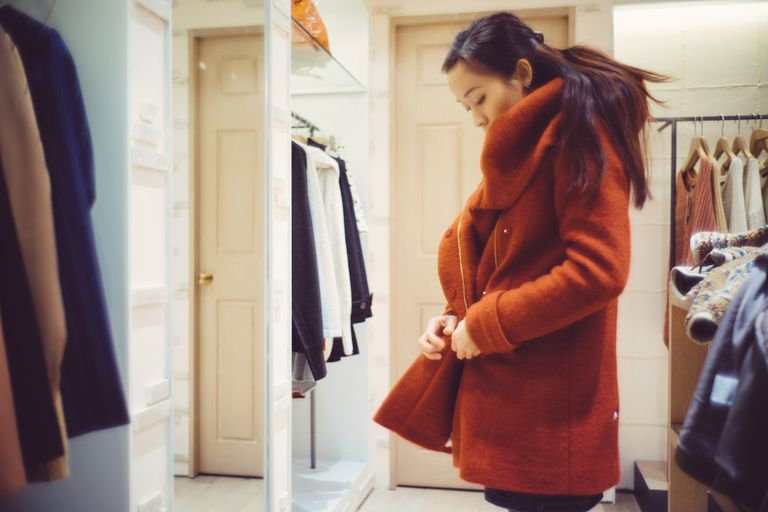 Young lady trying on a coat in the boutique