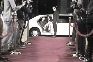 Bodyguard opening limousine for celebrity arriving at red carpet event