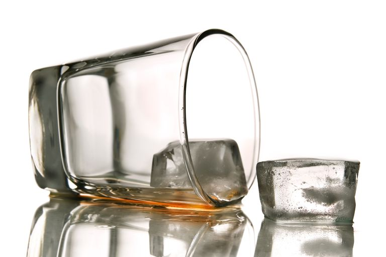empty alcohol glass tipped over with ice cubes spilling out