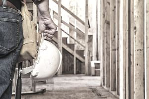 Construction Worker Closeup with Hardhat in Hand