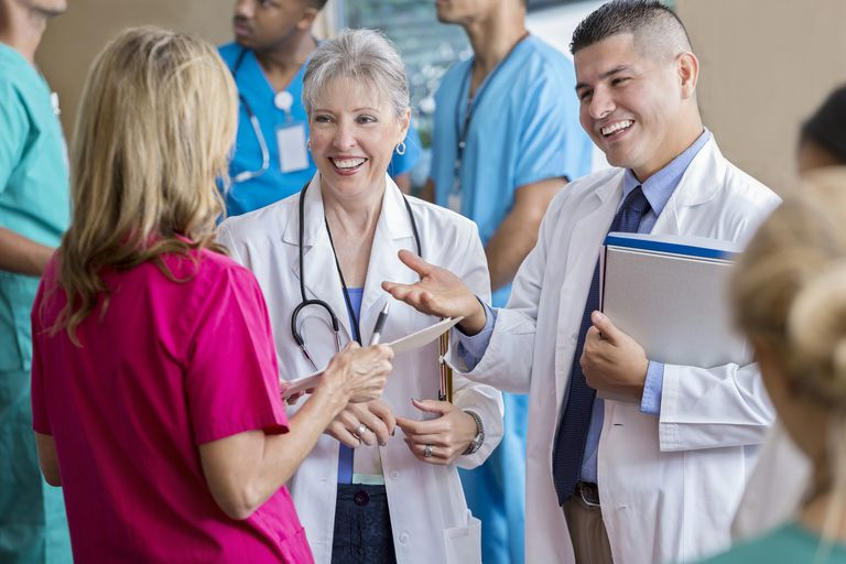 Handsome Hispanic doctor gestures while talking with colleagues