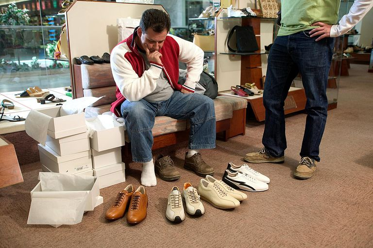 Man sitting on bench staring at selection of shoes, while another man looks on.