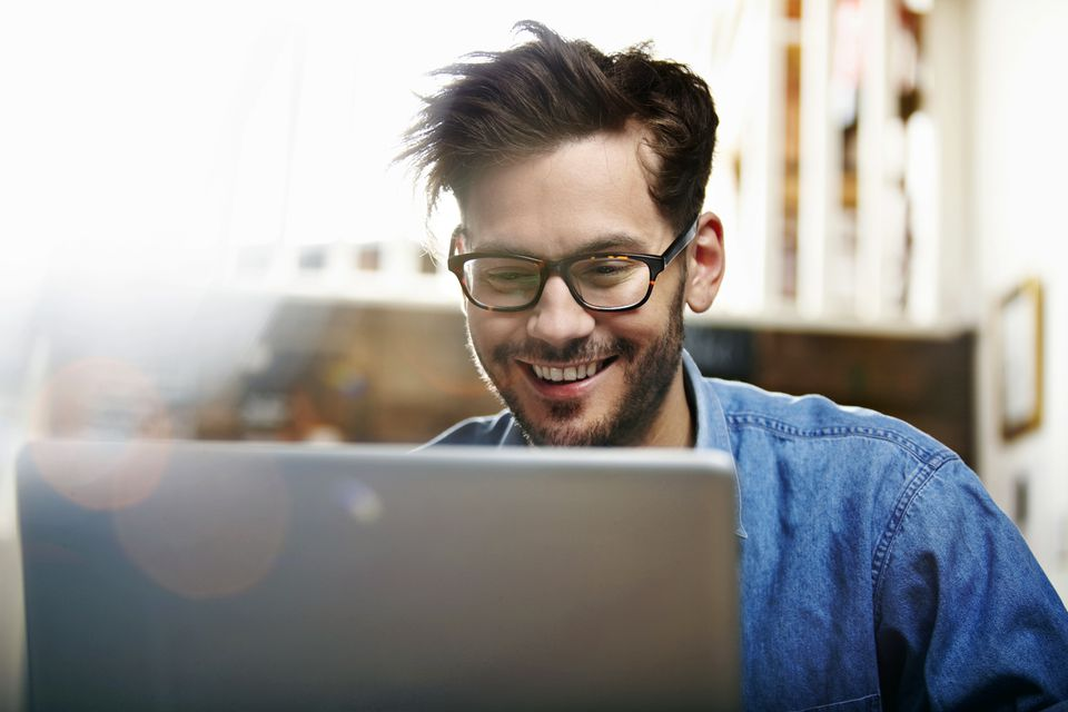 Happy man looking at laptop