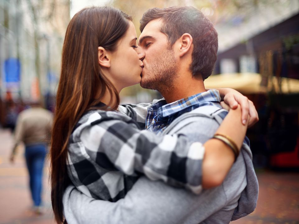 Young man and woman kissing in public
