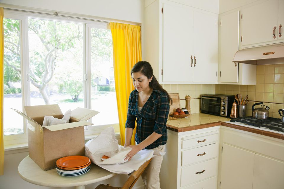 Woman packing plates into a box in her kitchen