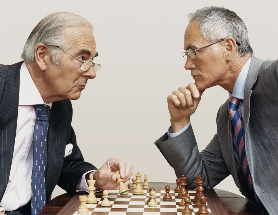 Two Businessmen Looking Face to Face and Playing Chess