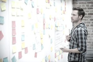 man brainstorming with sticky notes on wall