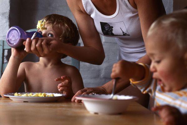 Mother helping children with breakfast