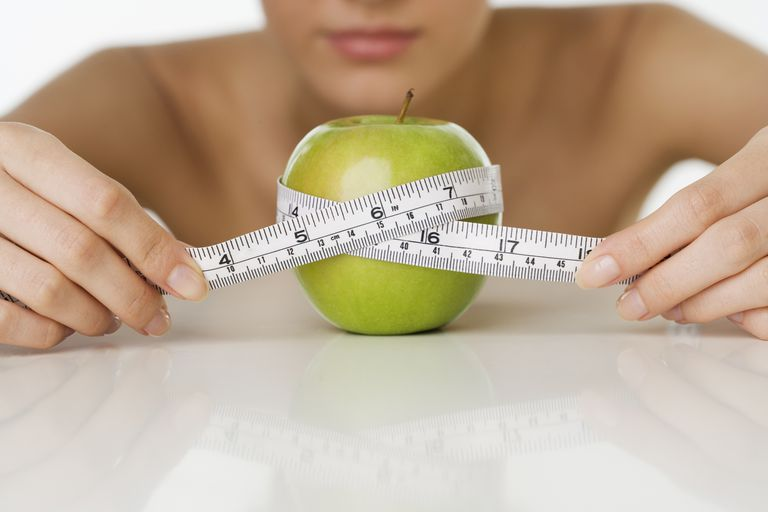 Woman measuring an apple