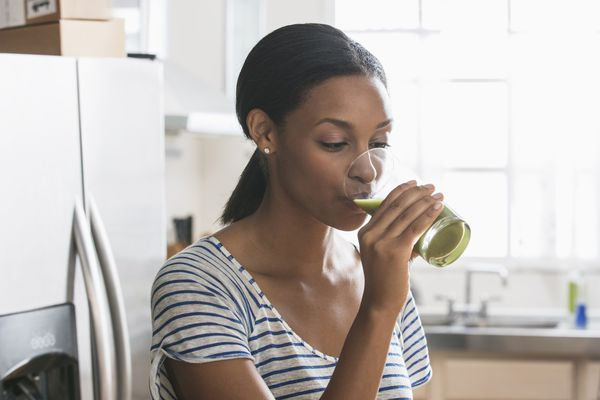 Woman drinking glass of green juice in kitchen