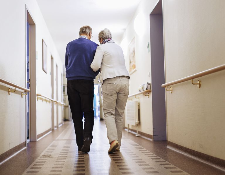 Senior Couple walking down the hallway of a care facility