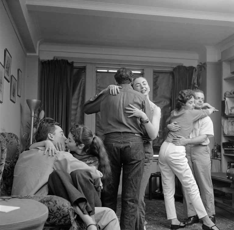 Group of 1960s teenagers kissing, hugging and dancing