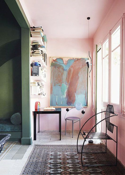 Globally decorated home office with pink walls and large artwork