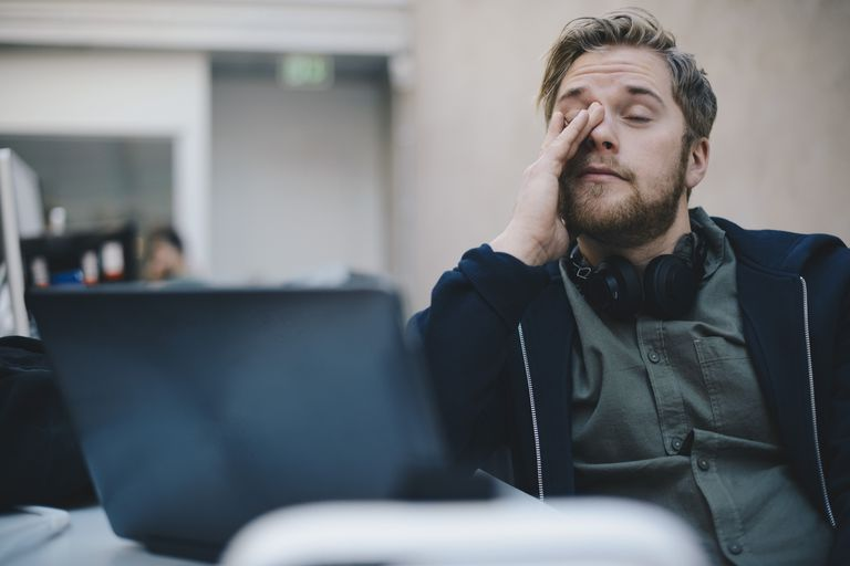 Tired computer programmer rubbing eyes while sitting in office