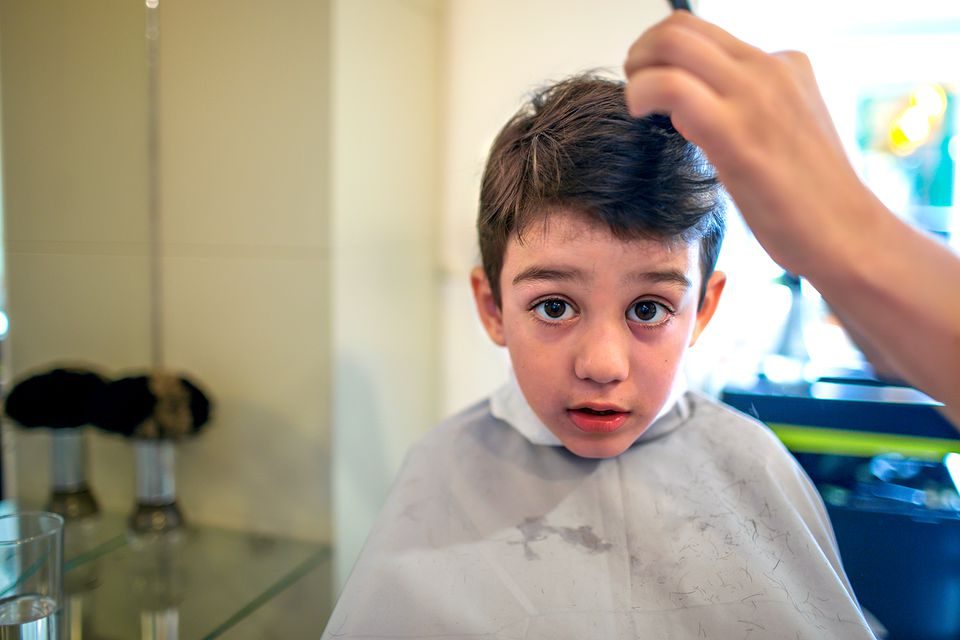 Young boy getting his hair cut