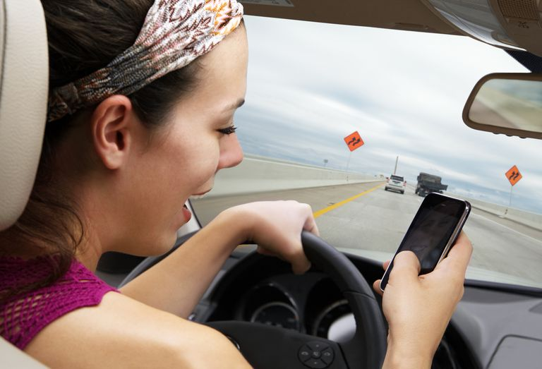 Young woman driving on highway while reading or writing text on smart phone.
