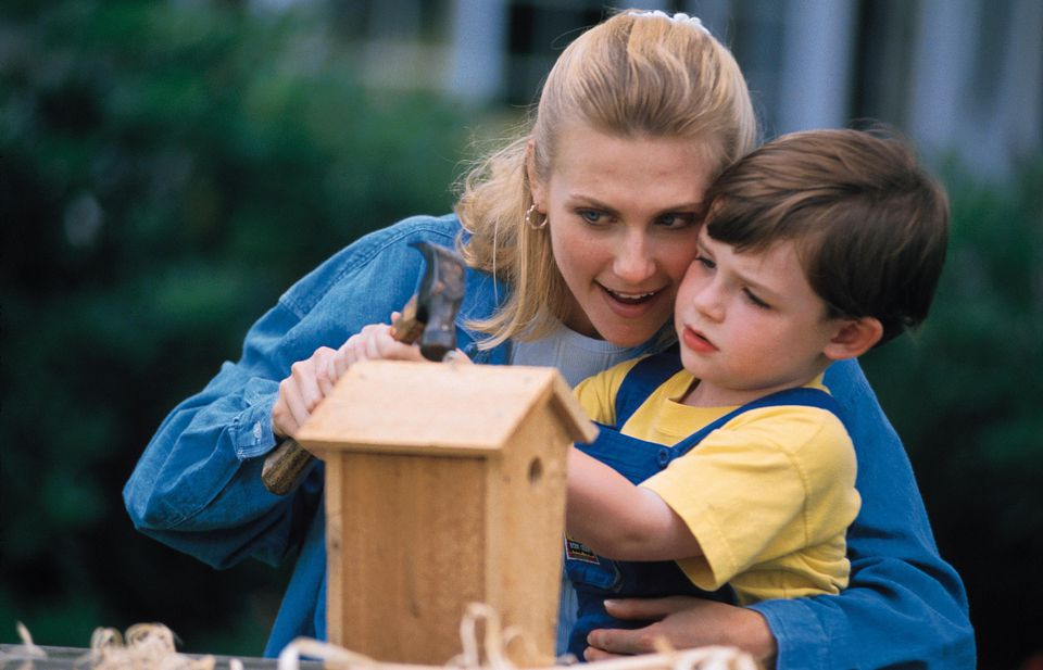 Mother and son building a birdhouse