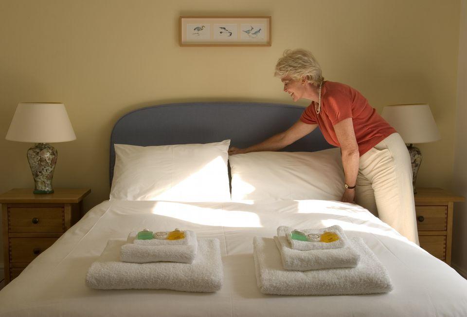 Woman adjusting pillows inside a hotel room, Start Point, Devon, England.