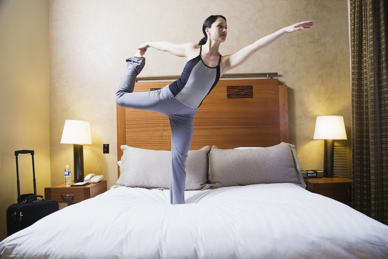 Woman doing yoga pose on a hotel bed