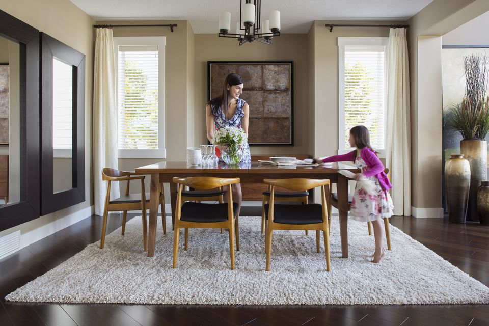 Mother and daughter setting dining room table