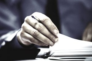 Male executive's hand holding pen, and lifting page of document