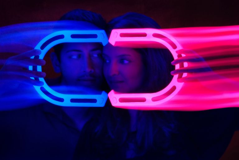 Young couple holding glowing magnets