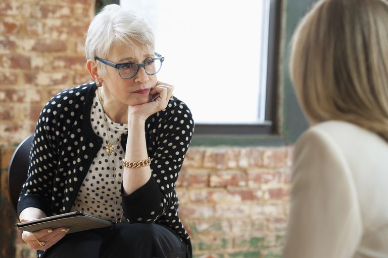 counselor with tablet talking to woman