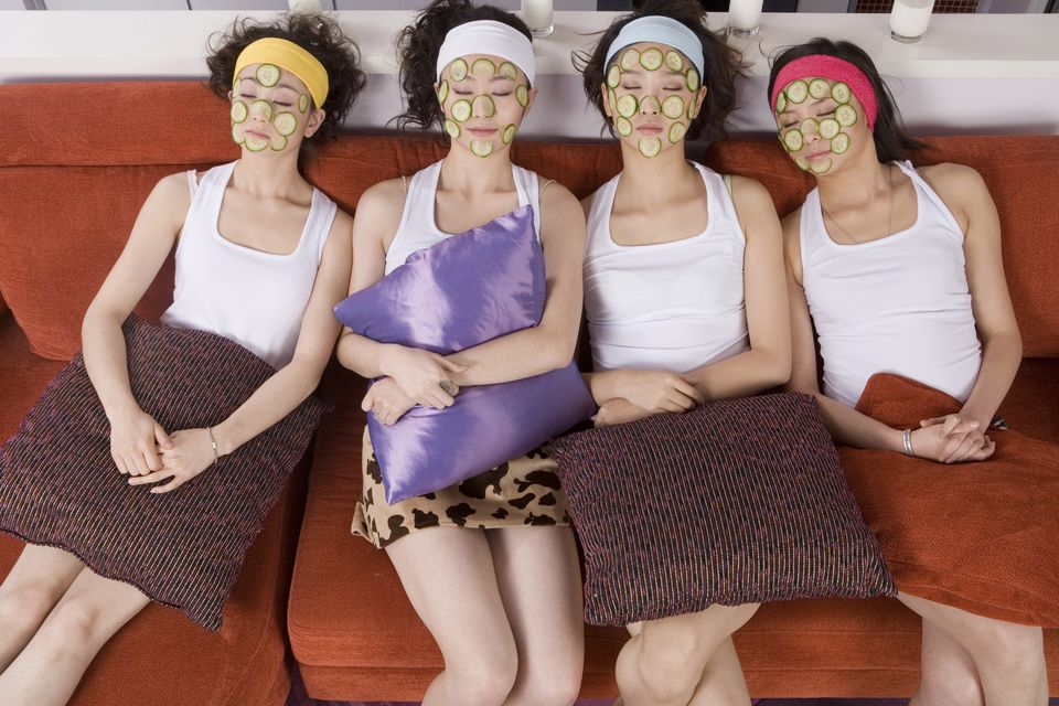 Four young woman with cucumber masks