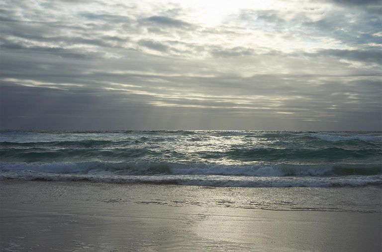 Sunshine bursts through the clouds as waves crash on an Atlantic coastline.
