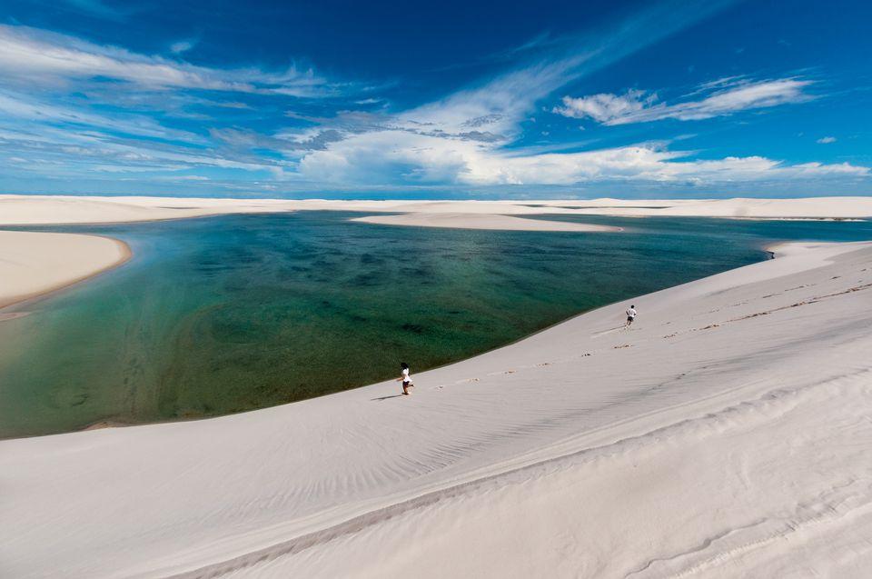 View of Maranhenses national park against blue sky and sand.