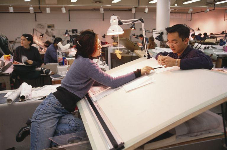 architecture school studio area, many drafting tables, students working together on projects