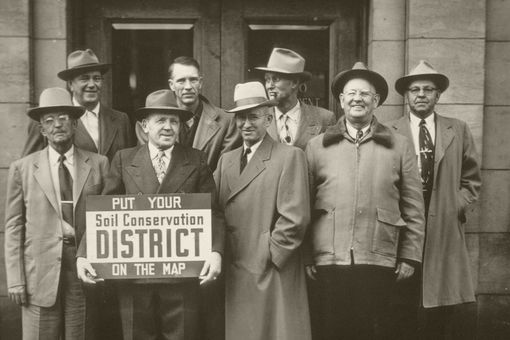 Men holding a Soil Conservation District sign.