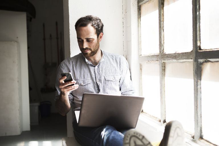 Man on phone and computer.