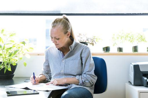 Woman doing paperwork in home office