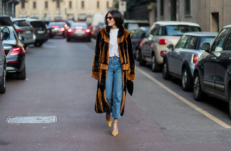 Street style fashion woman in fur coat and jeans