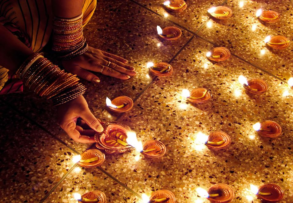 A woman's hand lighting Diwali diyas