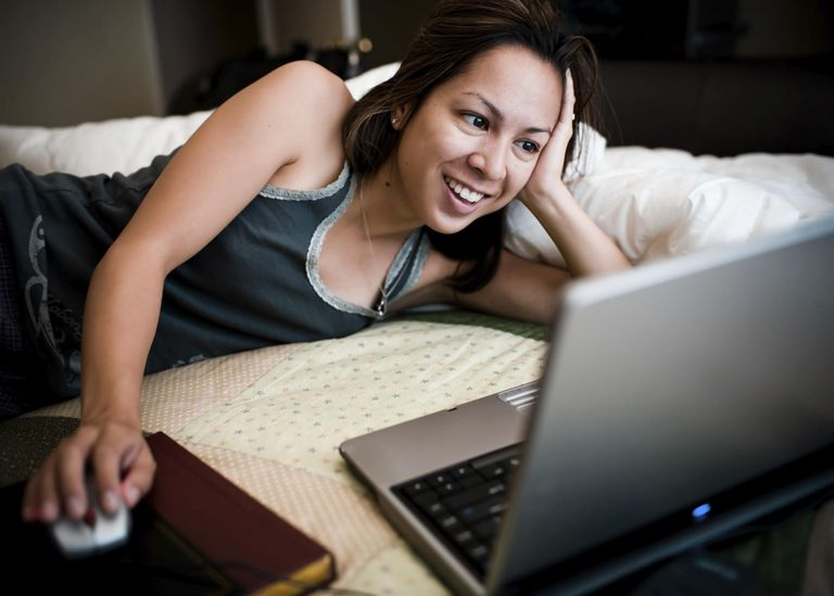female surfing the web on her bed