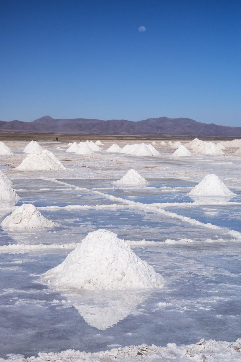 Salt mounds, extracted from salt plains, reflected in thin layer of water, Salar de Uyuni, Colchani, Bolivia, South America
