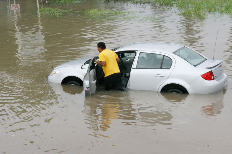 man checking car in flood