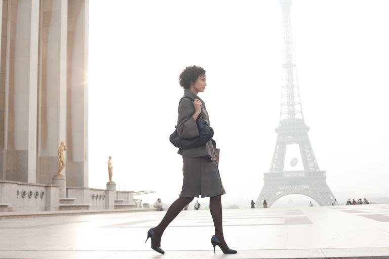 businesswoman walking in front of Eiffel tower